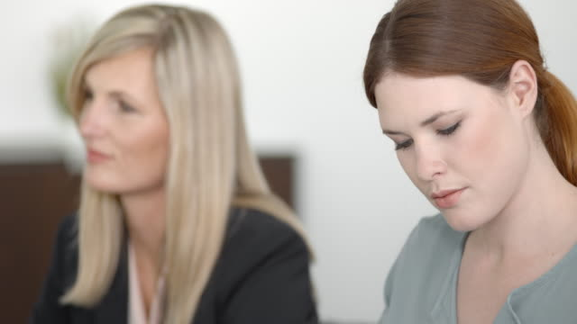 two female colleagues at a meeting with their coworkers - blazer video stock e b–roll