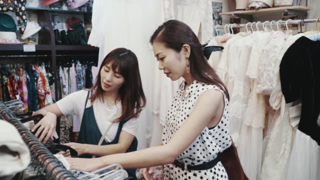 リサイクルショップでヴィンテージ衣類を一緒に買い物する2人の女性客 - オペレーター 日本人点の映像素材/bロール