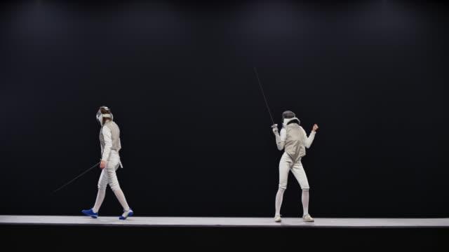 sro mo ld 兩個女擊劍運動員在比賽和一個慶祝贏得一分 - sword 個影片檔及 b 捲影像