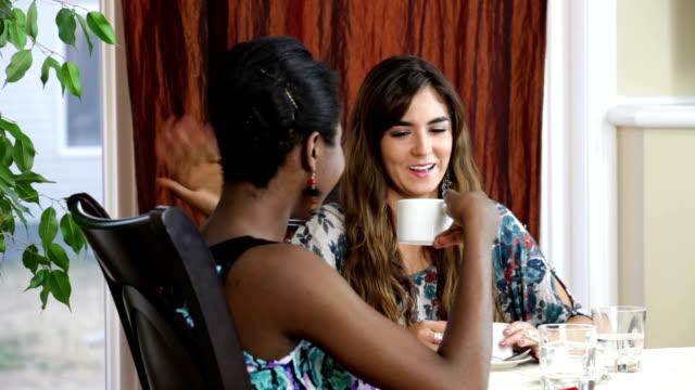 Two female friends drinking coffee video