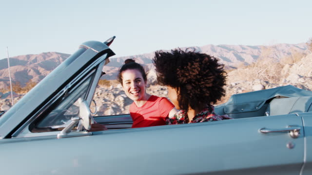 Two female friends driving an open car on a desert highway Two female friends driving an open car on a desert highway face to face stock videos & royalty-free footage
