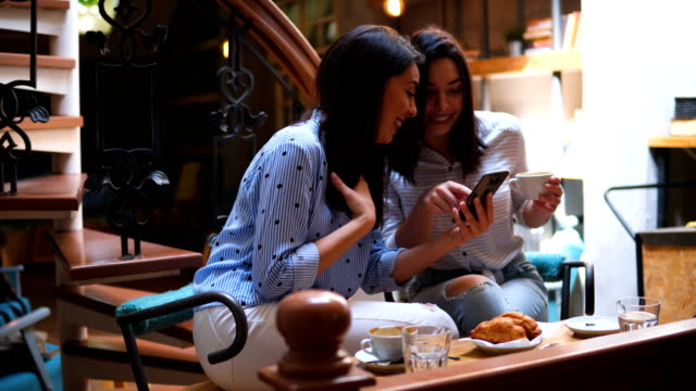 Two Female Friends Holding Smartphone and Chatting in Coffee Shop Two Female Friends Holding Smartphone and Chatting in Coffee Shop girlfriend stock videos & royalty-free footage