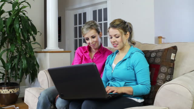 Two female friends in front of laptop computer video