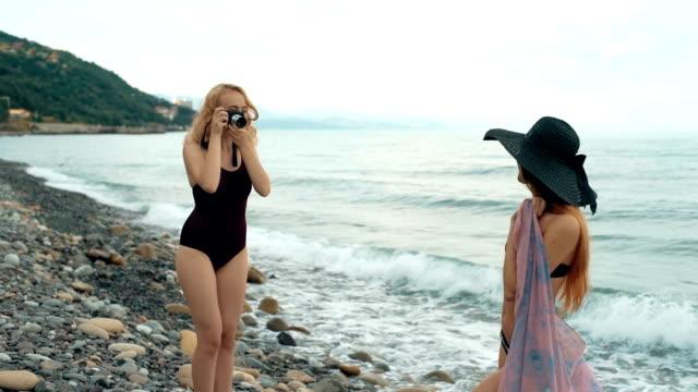 ビーチのカメラで写真を撮る水着で 2 つの女友達。レトロ コンセプト ビデオ