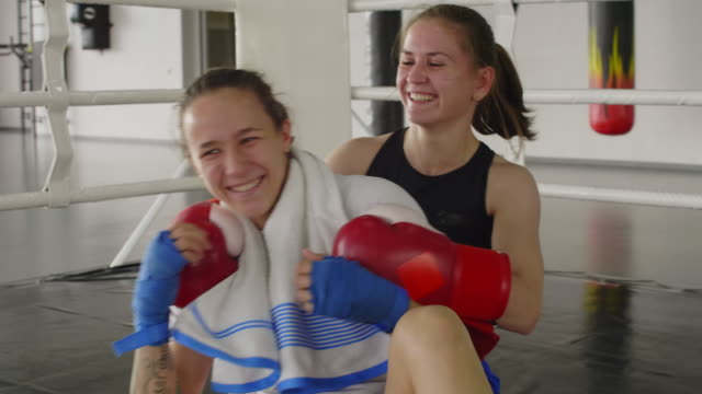 two female friends laughing and embracing after boxing workout on ring - guanto indumento sportivo protettivo video stock e b–roll
