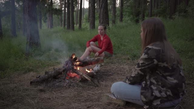 vídeos de stock, filmes e b-roll de duas amigas relaxando na fogueira na floresta - amizade feminina