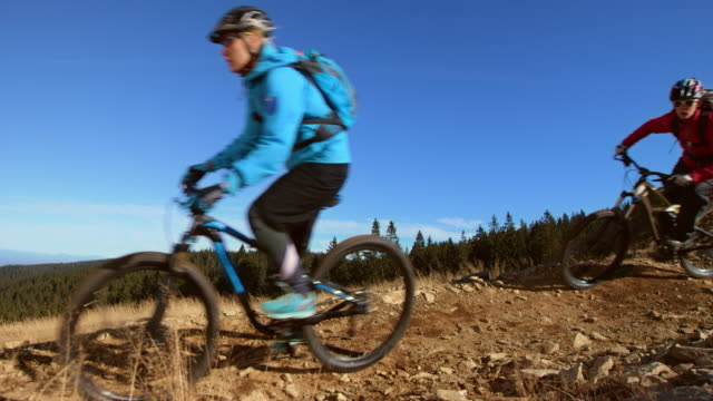 SLO MO Two female friends riding their bikes on a mountain trail video
