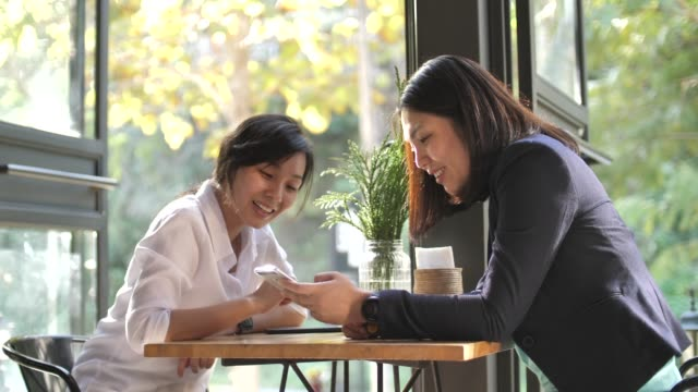 Two female friends sharing smartphone together in Cafe