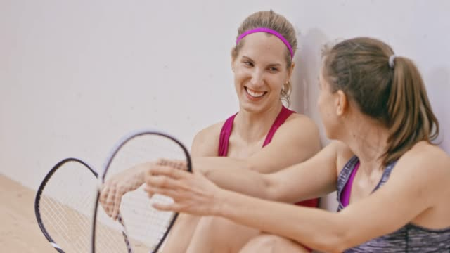 Two female friends sitting in the squash court after the game and chatting