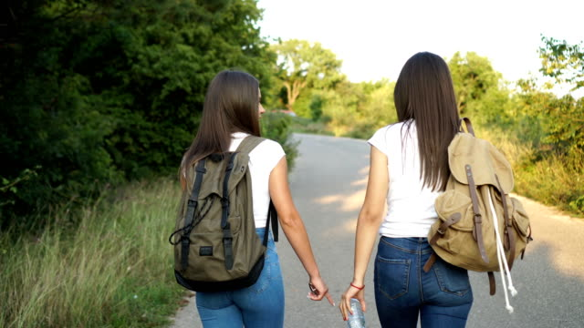 Two female friends walking along mountain road