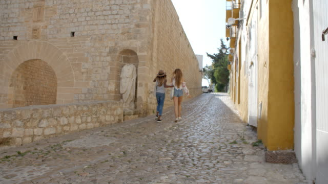 Two female friends walking through old Ibiza, back view video