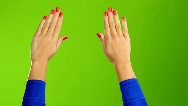 Two female hands waving hello or goodbye. Green screen background video