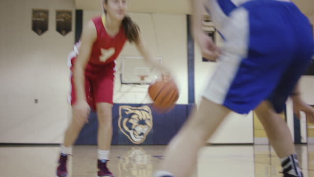 Two female high school basketball players competing against each other 1 on 1 during a game video