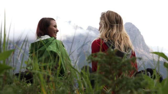 vidéos et rushes de deux randonneurs femelles relax sur le sentier de crête crête, couvert de jour - évasion du réel