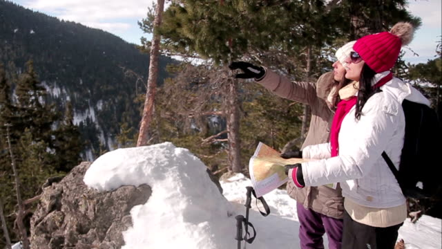 Two female hikers watch the map at the top of the mountain,winter scene video