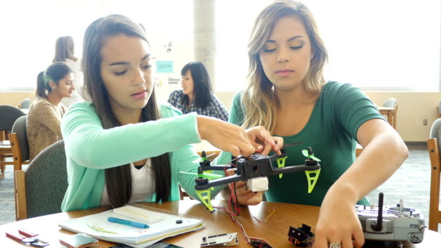 Two female Hispanic teenagers work together on robotics project at STEM school video