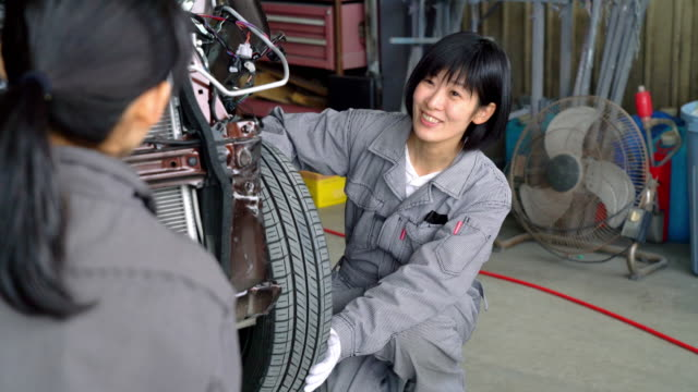 Two female mechanics working together in a car garage video