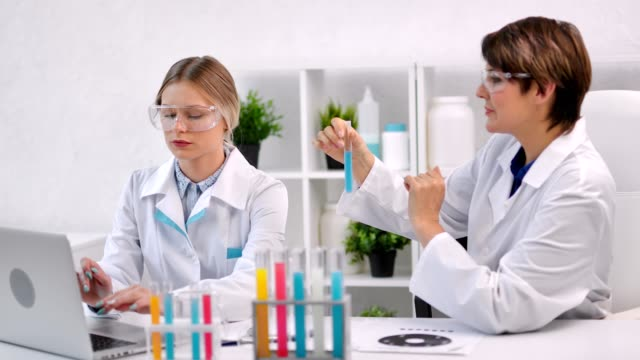 Two female medical scientist working with colorful liquid substance in tube using laptop pc