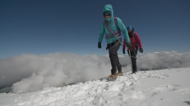 Two female mountaineers protected against the cold crossing a snowy glacier above the clouds.