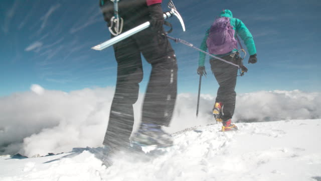 Two female mountaineers traverse a mountain ridge on a wind swept glacier at high altitude above the clouds.