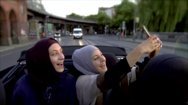 two female muslim friends riding in convertible car and taking selfies - etnia medio orientale video stock e b–roll