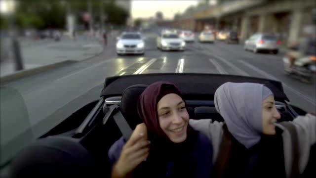 vídeos de stock, filmes e b-roll de dois amigos muçulmanos femininos andando em um carro conversível por berlim - dividindo carro