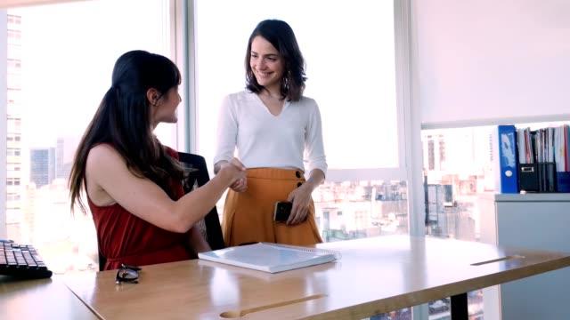 vídeos de stock e filmes b-roll de two female office coworker reach an agreement and shake hands 4k video - envolvimento dos funcionários