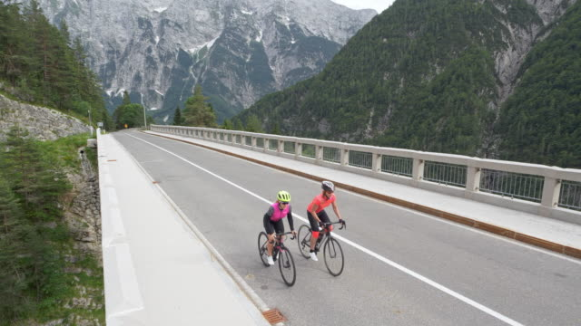 aerial two female road cyclists riding on a bridge across a gorge in the mountains - ciclismo su strada video stock e b–roll