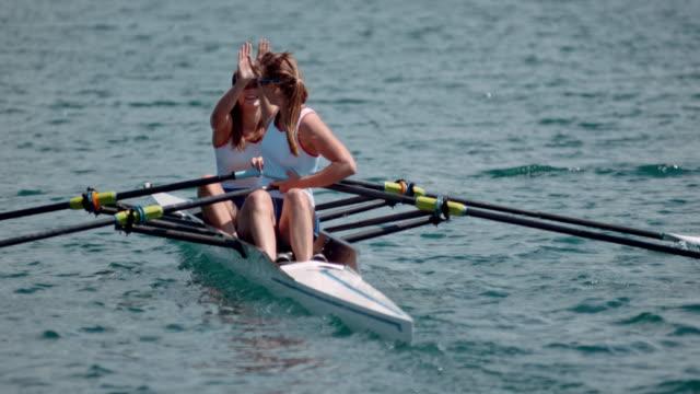 slo mo two female rowing athletes doing a high five on a double scull - wiosłować ćwiczenie fizyczne filmów i materiałów b-roll