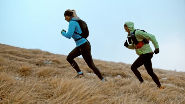 slo mo two female runner running up a grassy slope on a cold day - 40 49 lat filmów i materiałów b-roll