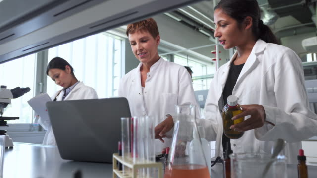 Two female scientists talking about their experiments in the laboratory