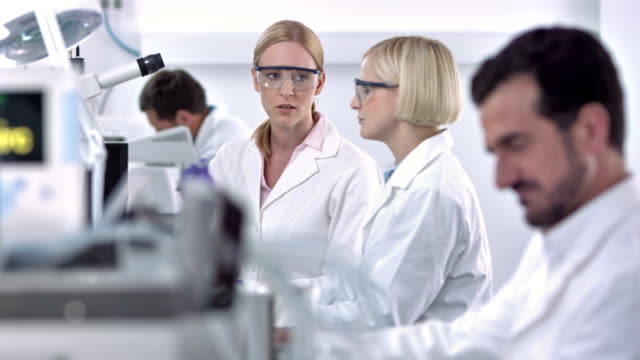 LS DS Two Female Scientists Working Together HD1080p. LONG DOLLY shot of two female scientists discussing about laboratory results. lab coat stock videos & royalty-free footage