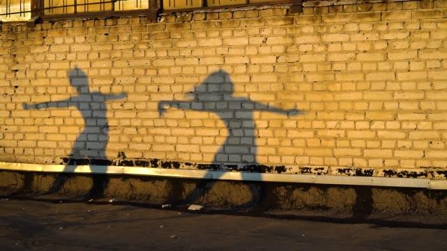 日没時に屋根のレンガの壁に対して踊る2人の女性のシルエット - バレエ点の映像素材/bロール