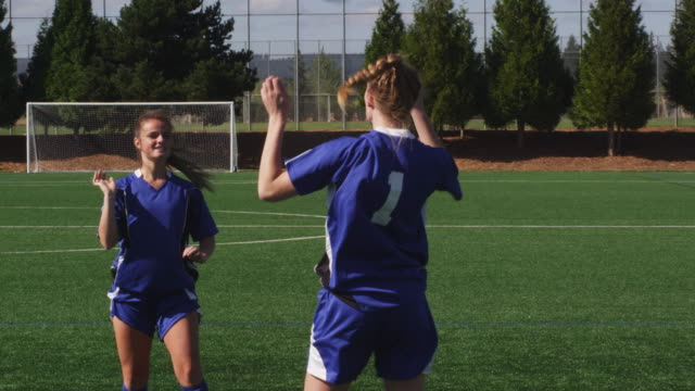 Two female soccer players heading a ball back and forth video
