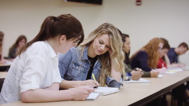 Dois estudantes do sexo feminino tendo discussão em sala de aula - vídeo