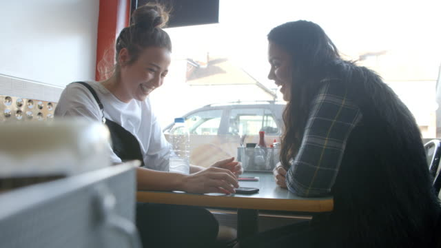 Two Female Students In Cafe Check Messages On Mobile Phone video