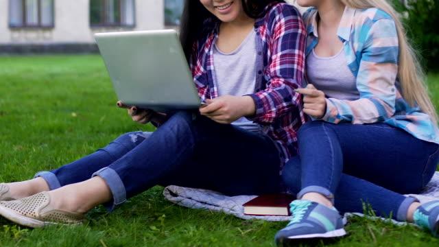 vídeos y material grabado en eventos de stock de dos alumnas en césped que laptop y conversación, amistad - baile de estudiantes de secundaria