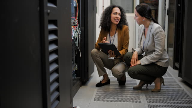 LD Two female technicians squatting in the server room discussing connections video