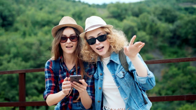 two female travelers in the mountains discussing and looking on a smartphone during a hike - wildlife travel stock videos & royalty-free footage