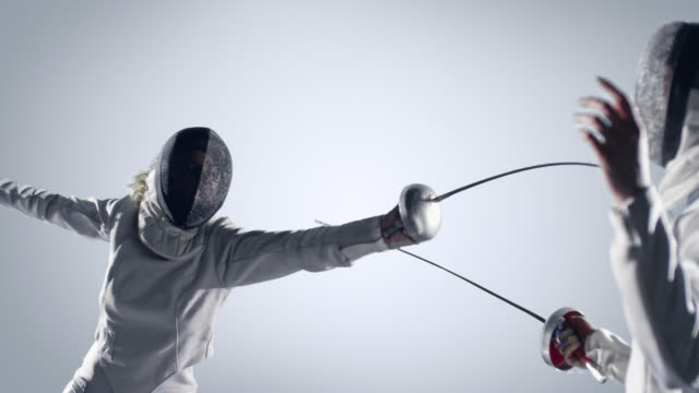 Two fencing sportswomen  in action on white background video