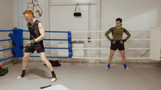 vídeos y material grabado en eventos de stock de dos luchadores están teniendo un entrenamiento intensivo en el club de combate en el ringside. - coordinación