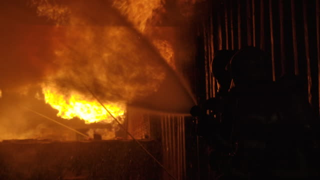 Two firefighter on duty in Burning Building.Two firefighters fighting a fire with a hose and water during a firefighting.