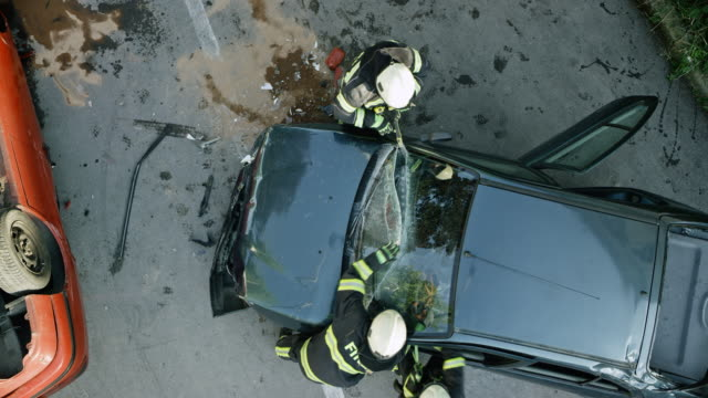 CS Two firefighters cutting through the windshield of a crashed car at the scene of a car accident Wide crane shot of two firefighters cutting the windshield of the car crashed in a car accident. Shot in Slovenia. car accident stock videos & royalty-free footage