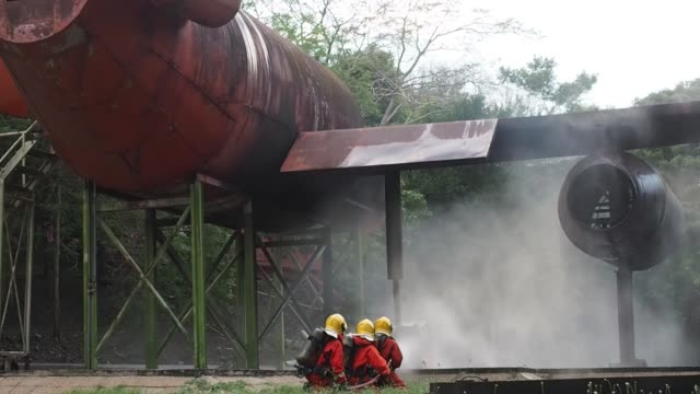 Two Firefighters training are spraying high pressure water fire fighting operation,