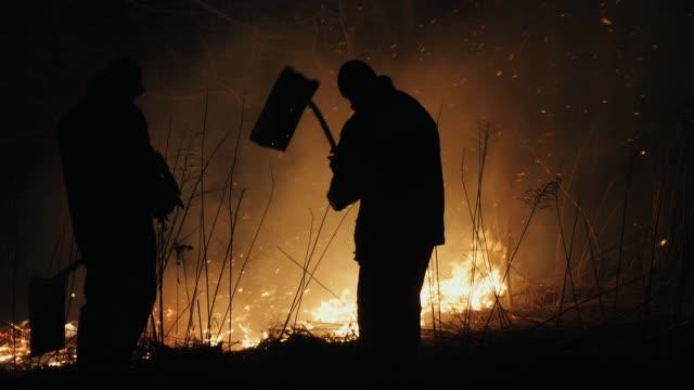 vidéos et rushes de deux pompiers avec des flappers de feu éteints un feu dans la forêt la nuit - desastre natural