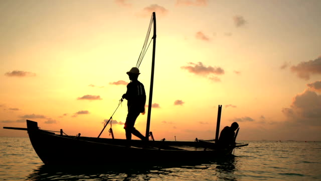 Two fishermen scooped water out of an old wooden boat at the end of a hard day at sunset in the Indian Ocean Two fishermen scooped water out of an old wooden boat at the end of a hard day at sunset in the Indian Ocean recreational boat stock videos & royalty-free footage