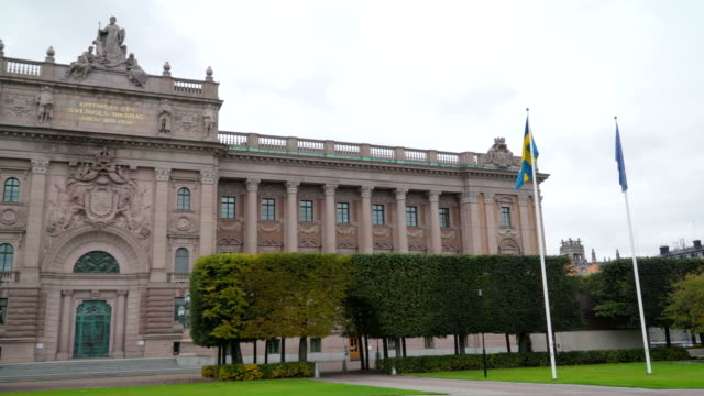 Two flags on the pole outside the national legislature building in Stockholm Sweden Two flags on the pole outside the national legislature building in Stockholm Sweden found outside the grassy lawn of the building royalty stock videos & royalty-free footage