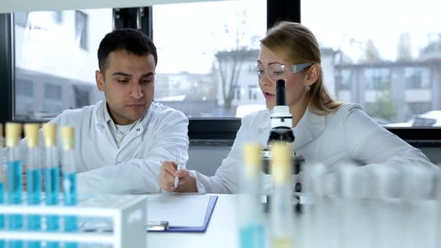 Two focused scientists doing microscope analysis video