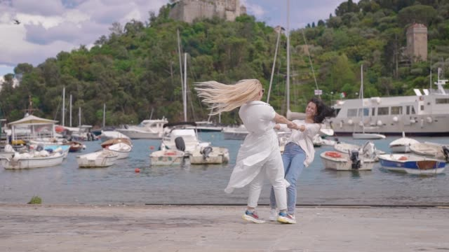 Two friends are having fun in Italian portofino. Funny spinning and holding hands. Resort