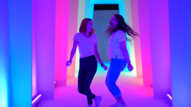 vídeos de stock, filmes e b-roll de dois amigos dançando e se divertindo no túnel colorido - cor vibrante